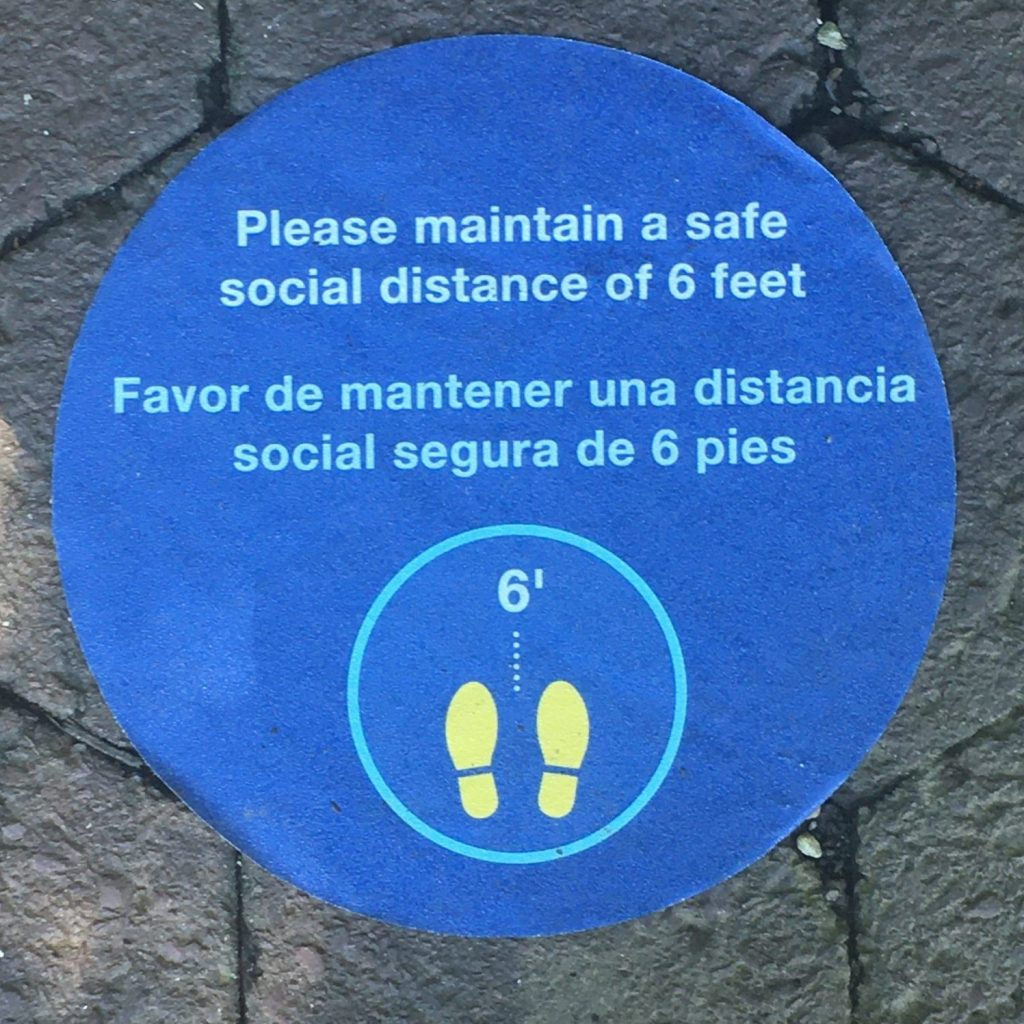 "A blue circle with the words ""Please maintain a safe social distance of 6 feet / Favor de mantener una distancia social segura de 6 pies"" A womans toes are visible below the graphic."