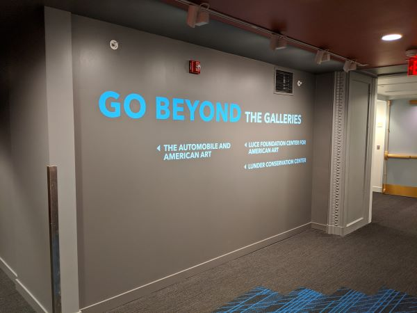 "Blue letters on a gray wall reading ""Go Beyond the Galleries"""