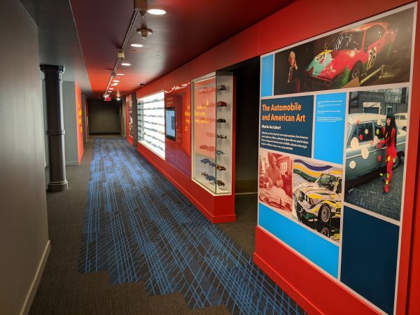 A view of a red hallway showing graphic panels and display cases