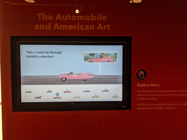 "A monitor displaying a pink Cadillac and the words ""Take a road trip through SAAM's collection!"""