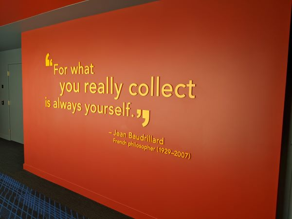 "Yellow letters on a red wall reading ""For what you really collect is always yourself. -Jean Baudrillard, French philosopher (1929-2007)"