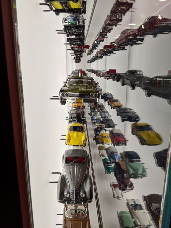 A close-up view of model cars in a display case showing their reflection on the glass.