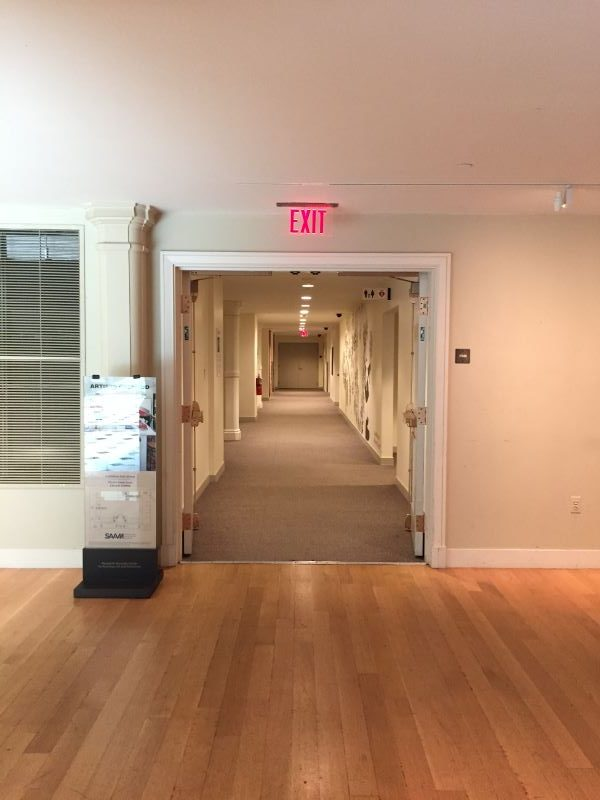 A view of a white hallway with a gray carpet