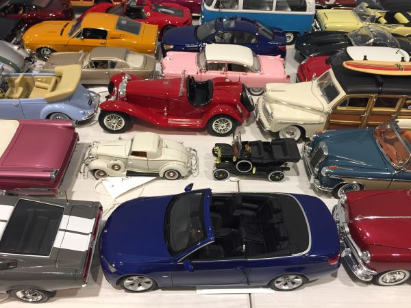 Model cars of various sizes and colors lined up on a table seen from the side