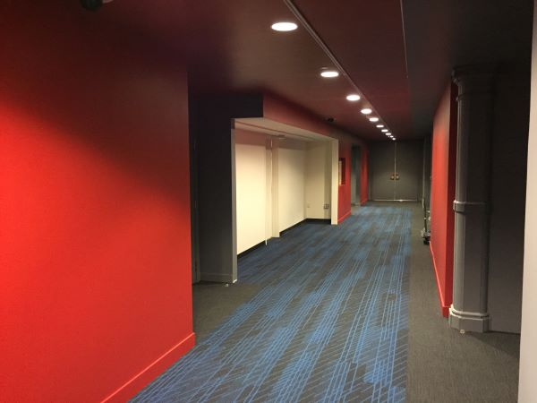 An empty hallway with red walls and a gray and blue carpet