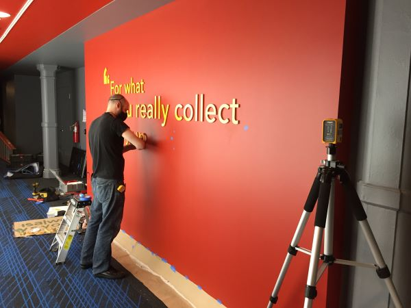 A man wearing a mask installs yellow dimensional letters on a red wall.