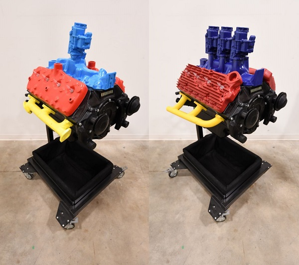 Split-screen image showing two versions of the engine prototype. The version on the left includes light blue, red, and yellow parts. The version on the right includes dark blue, red, and yellow parts.