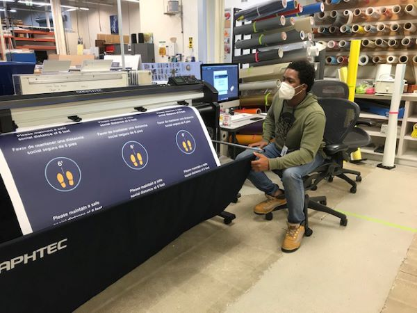 A man wearing a face mask sits next to a machine which is cutting a large print into smaller graphics.