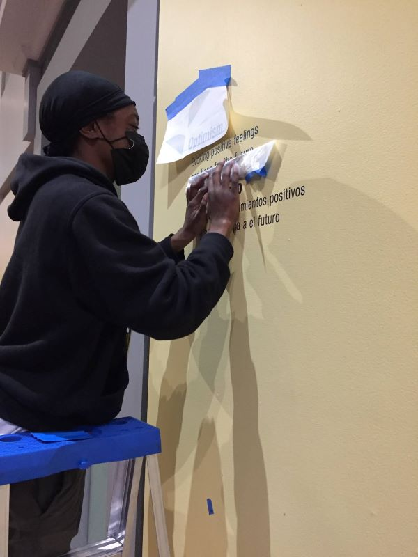 A young woman wearing a skull cap and a face mask stands on a ladder and applies vinyl letters to a yellow wall.
