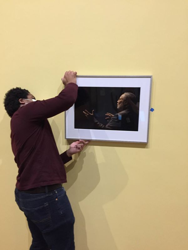 A young man wearing a face mask hangs a framed photo of a man on a wall.