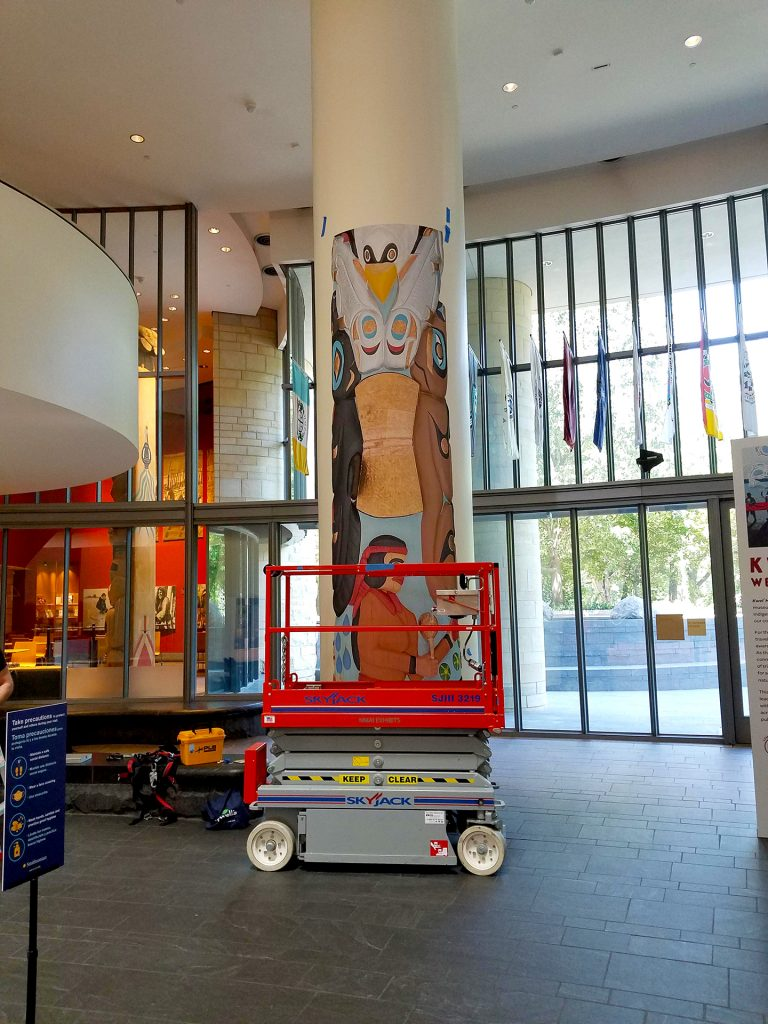 Installation of the Kwel' Hoy Totem Graphic onto the column at the museum. Fork lift is used for the installation