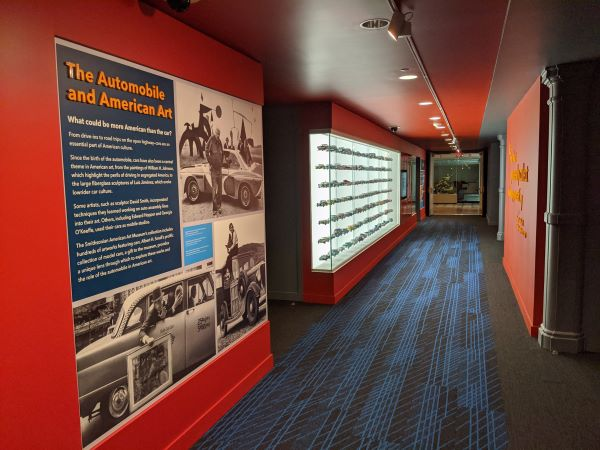 A view of a red hallway showing a graphic panel and a backlit display case