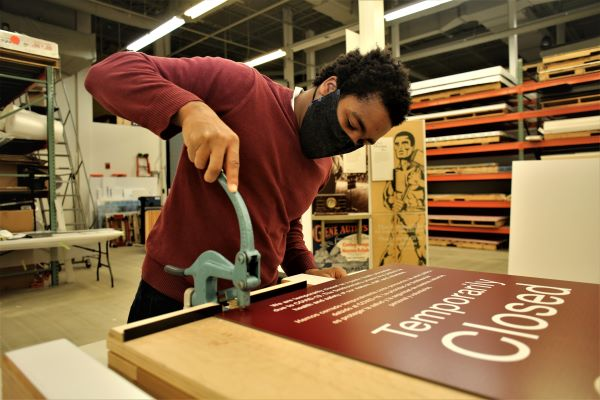 """A young man wearing a face mask pushes down on a hole punch on top of a sign that reads """"Temporarily Closed."""""""